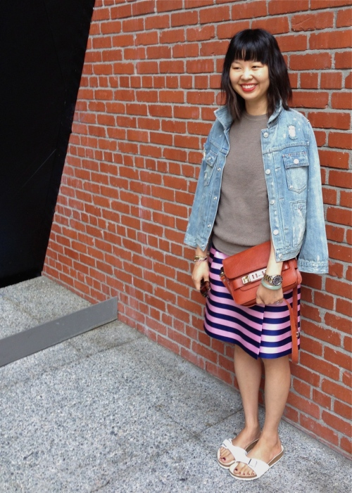 distressed denim jacket over satin stripe skirt and white birkenstocks